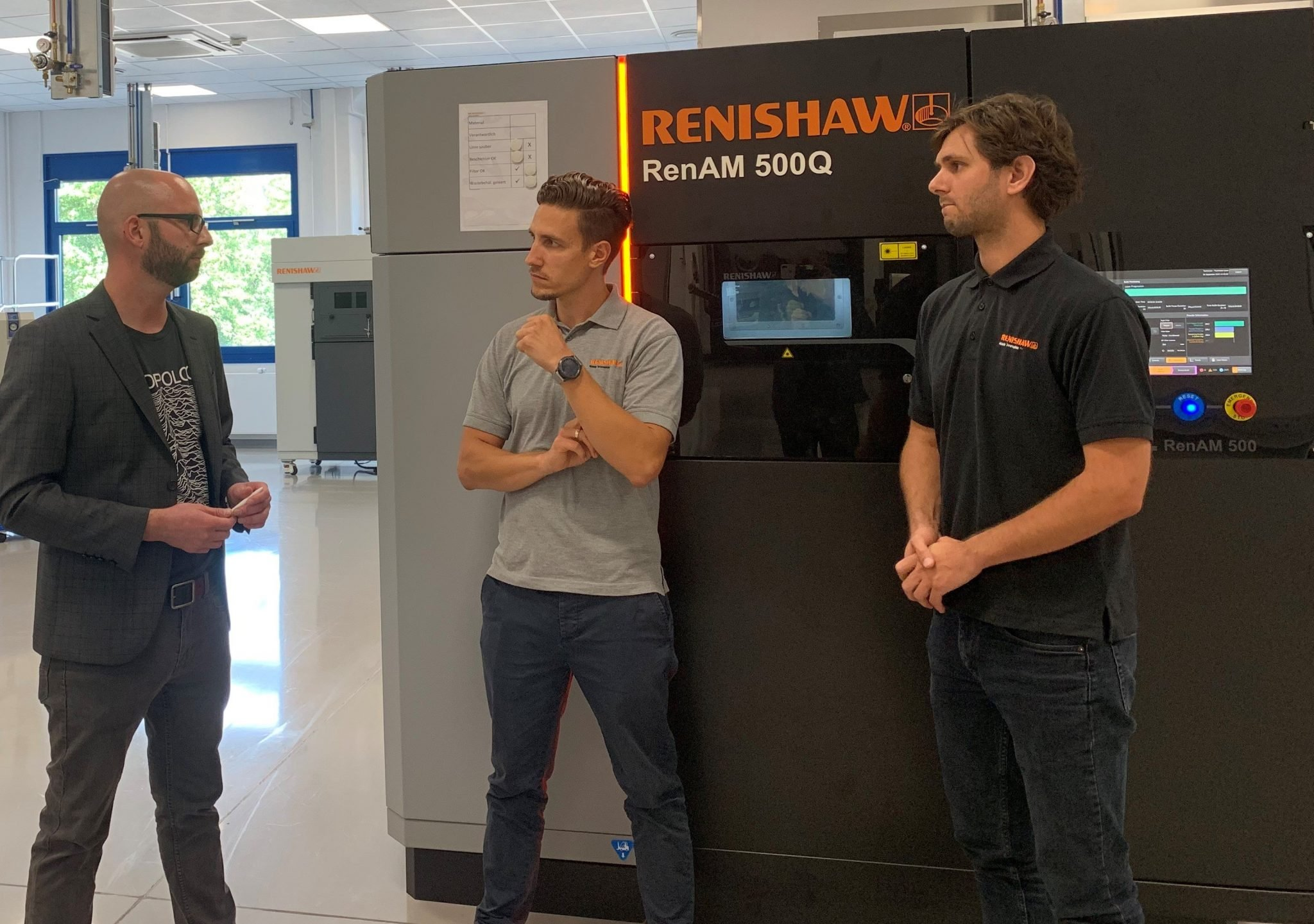 nTopology and Renishaw Employees in front of a RenAM 500Q 3d Printer