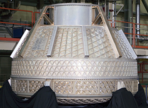 Machined metal isogrid on a spacecraft capsule. The high cost to get vehicles to orbit motivates advanced lightweighting techniques.
