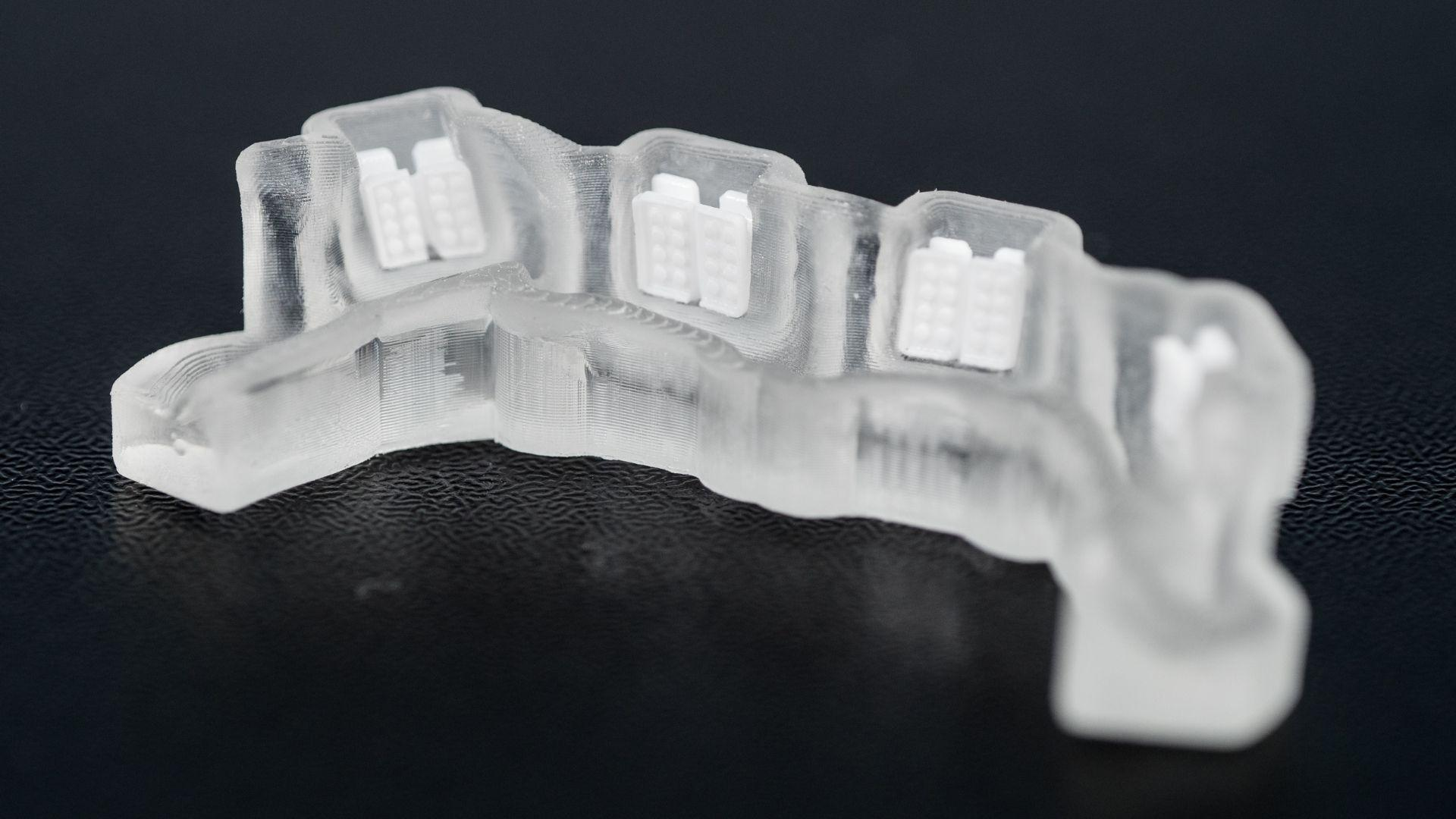 Closeup of LightForce's 3D printed custom dental braces and tray designed in nTopology